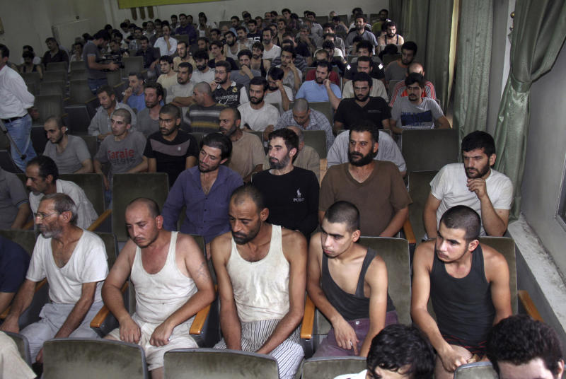 FILE - In this Sept. 1, 2012 file photo, Syrian detainees who took part in anti-government protests sit in a courtroom before their release, in Damascus. Syrian activists said Thursday a prominent rights lawyer believed to be in government custody for more than eight months is suffering from deteriorating health and called for his immediate release. (AP Photo/Bassem Tellawi, File)