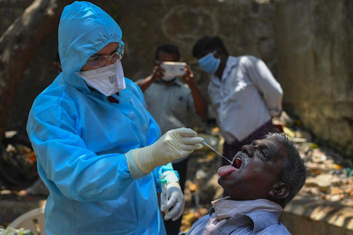 A doctor takes a swab sample at a COVID-19 coronavirus testing drive inside the Dharavi slums during a government-imposed nationwide lockdown as a preventive measure against the spread of the COVID-19 coronavirus, in Mumbai on April 16, 2020. (Photo by INDRANIL MUKHERJEE / AFP) (Photo by INDRANIL MUKHERJEE/AFP via Getty Images)