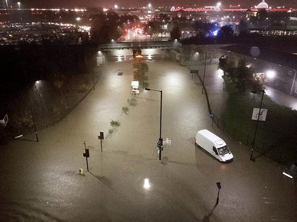 A flooded road in Sheffield. Meadowhall shopping centre, where people were forced to spend the night, is visible in the background. Photograph: Lee Parkinson