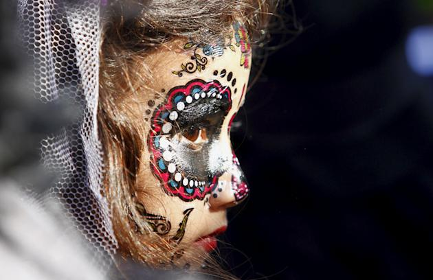 A girl with her face painted to look like 'Catrina' at a Day of the Dead celebration Mexico (Reuters)
