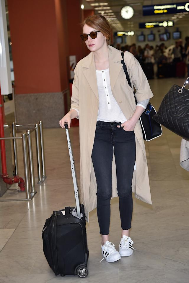 <p>Stone wears a white henley, oversized tan overcoat, and Adidas sneakers while traveling. (Photo: Getty) </p>