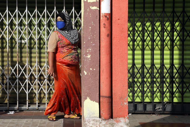 Rohingya woman walks past closed shops in Kuala Lumpur