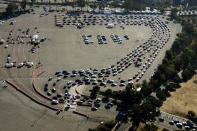 FILE - In this Nov. 18, 2020, file photo, long lines of motorists wait to take a coronavirus test in a parking lot at Dodger Stadium in Los Angeles. With the coronavirus surging out of control, the nation's top public health agency advised Americans on Thursday, Nov. 19, not to travel for Thanksgiving and not to spend the holiday with people from outside their household. (AP Photo/Ringo H.W. Chiu, File)