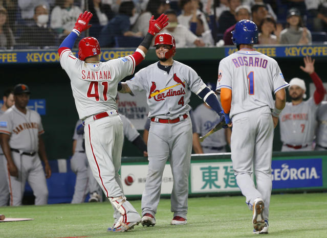 MLB All-Star first baseman Carlos Santana (41) of the Philadelphia Phillies celebrates with teammates Yadier Molina (4) of the St. Louis Cardinals and Amed Rosario (1) of the New York Mets after hitting a three-run home-run off All Japan's pitcher Kakeru Narita in the 5th inning of Game 1 of their All-Stars Series baseball at Tokyo Dome in Tokyo, Friday, Nov. 9, 2018. (AP Photo/Toru Takahashi)