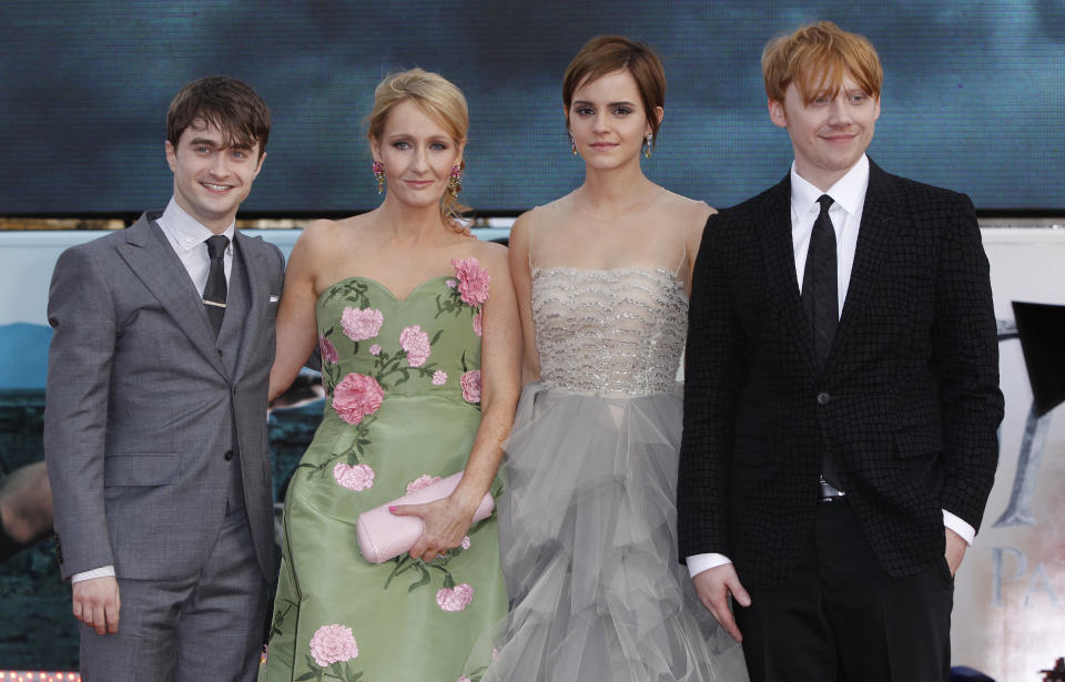 """British author JK Rowling, second left, joins actors, left to right, Daniel Radcliffe, Emma Watson and Rupert Grint in Trafalgar Square, central London, for the World Premiere of """"Harry Potter and the Deathly Hallows: Part 2"""" the last film in the series, Thursday, July 7, 2011. Harry Potter's saga is ending, but his magic spell remains. Thousands of fans from around the world massed in London Thursday for the premiere of the final film in the magical adventure series. (AP Photo/Joel Ryan)"""