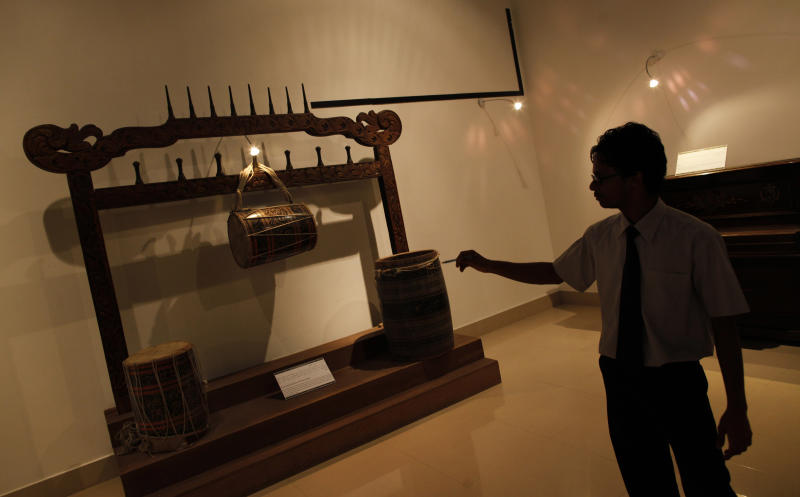 Ismail Ashraf, assistant curator  points at a 12th century pre-Islamic artifact at the Maldives national museum in Male, Maldives, Tuesday, Feb. 14, 2012. The museum is reopening without some of its most valuable exhibits a week after a mob of suspected religious extremists smashed images from the pre-Islamic era of this Indian Ocean archipelago. The mob of apparent Muslim extremists attacked the museum during the Maldives' unfolding political crisis. The country has seen weeks of protests and last week the president stepped down. He later said he was forced to resign at gunpoint. .(AP Photo/ Gemunu Amarasinghe)