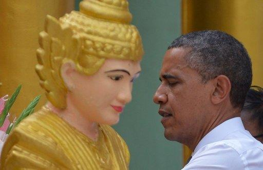 <p>US President Barack Obama performs a ritual during a visit to the Shwedagon pagoda in Yangon. Miles of smiles lit up shabby Yangon Monday during a visit by Obama, a striking contrast to the wrenching, dark years under a xenophobic junta.</p>