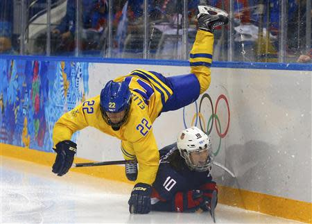 Sweden's Eliasson falls over Team USA's Duggan during the third period of their women's semi-final ice hockey game at the 2014 Sochi Winter Olympics