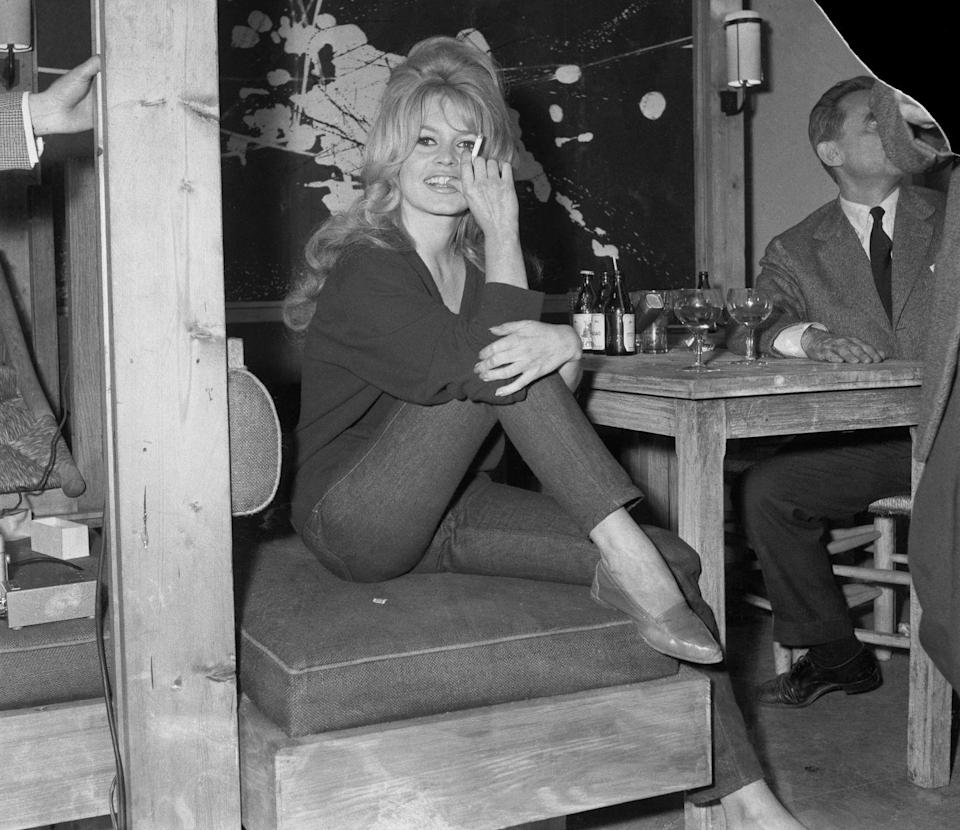 <p>Looking effortlessly chic, Brigitte Bardot paired an oversized sweater with dark wash cigarette jeans and loafers on the set of her film, <em>La Verite</em>. The French actress made sure to sport her signature bouffant as well. </p>