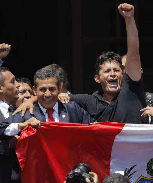 "Peru's President Ollanta Humala, left, holds a Peruvian national flag during a rally celebrating the United Nations' highest court ruling on a maritime boundary between Peru and Chile, at government palace in Lima, Peru, Monday, Jan. 27, 2014. The United Nations' highest court set a maritime boundary between Chile and Peru on Monday that grants Peruvians a bigger piece of the Pacific Ocean while keeping rich coastal fishing grounds in the hands of Chilean industry. Humala, a retired army officer when he was elected Peru's president, called Monday ""one of the days that will mark my life, and I feel proud to have lived as a soldier and now as a politician. I feel prouder every day to be Peruvian."" (AP Photo/Juan Diego Contreras)"