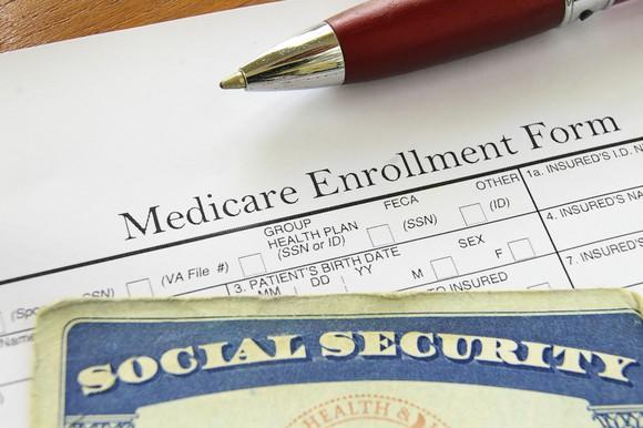 Medicare enrollment form with Social Security card on top.