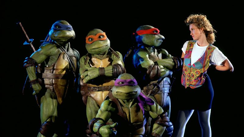 A publicity still for Teenage Mutant Ninja Turtles shows Leonardo, Michaelangelo, Donatello, Raphael and Judith Hoag as reporter April O'Neil. (New Line Cinema)