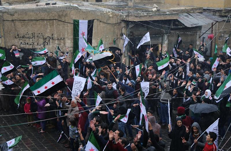 Syrians wave their national flag and Islamist flags in the old city of the northern Syrian city of Aleppo during a rally marking the fifth anniversary of the start of the conflict (AFP Photo/Baraa Al-Halabi)