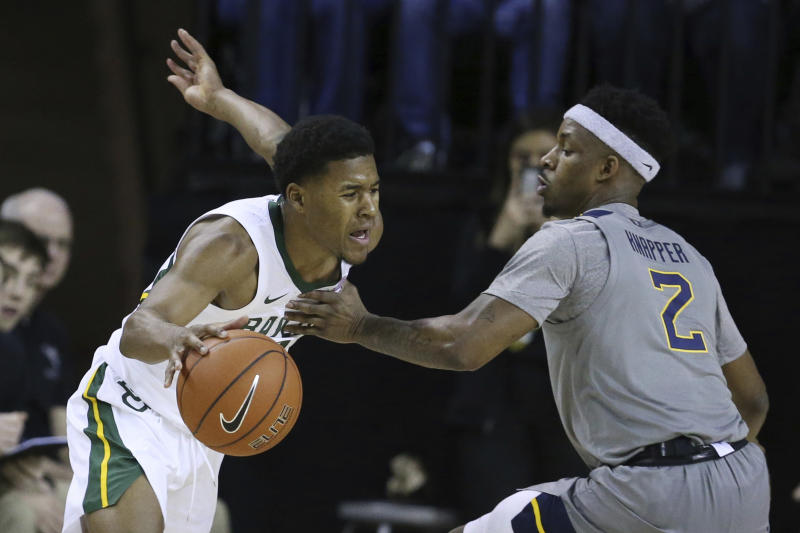 Baylor guard Jared Butler, left, is guarded by West Virginia guard Brandon Knapper, right, in the first half of an NCAA college basketball game, Saturday, Feb. 15, 2020, in Waco, Texas. (AP Photo/Rod Aydelotte)