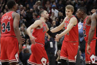 Chicago Bulls guard Zach LaVine, second from left, celebrates with teammates after scoring the game- winning score against the Los Angeles Clippers during the second half of an NBA basketball game Saturday, Dec. 14, 2019, in Chicago. The Bulls won 109-106. (AP Photo/Nam Y. Huh)