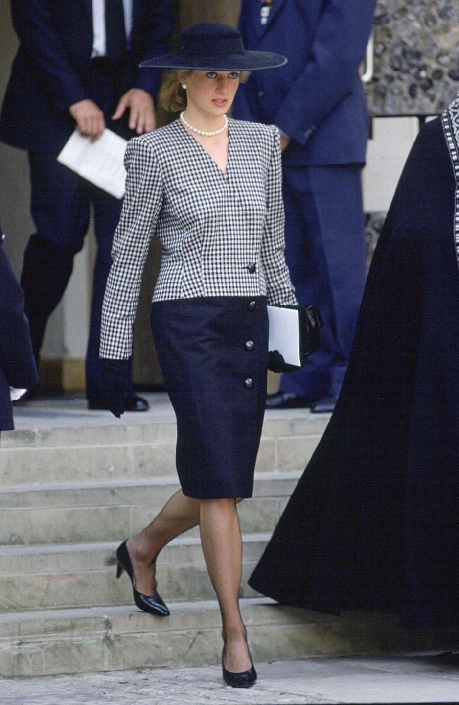 <p>In a gingham blazer and navy skirt, pumps, and hat while attending a memorial service for the the victims of the Marchioness Disaster. </p>