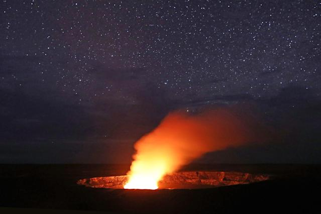 <p>Stars shine above as a plume rises from the Halemaumau crater, illuminated by glow from the crater's lava lake, within the Kilauea volcano summit at the Hawaii Volcanoes National Park on May 9, 2018 in Hawaii Volcanoes National Park, Hawaii. (Photo: Mario Tama/Getty Images) </p>