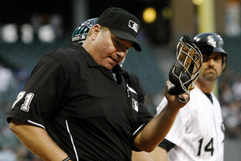 FILE - In this July 28, 2010 file photo, home plate umpire Brian Runge reacts after being hit in the mask by a foul ball off the bat of Chicago White Sox's Paul Konerko during the first inning of Chicago's baseball game against the Seattle Mariners in Chicago. Two people familiar with the situation tell The Associated Press that a Major League Baseball umpire was recently dismissed for what was believed to be the first known drug ouster among umps. The two people tell the AP that Runge failed at least one drug test, then reached an agreement so he could remain on the umpire roster. When he failed to comply with those terms, he was released. The people spoke on condition of anonymity because MLB didn't publicly say why Runge was gone. (AP Photo/Charles Rex Arbogast, File)
