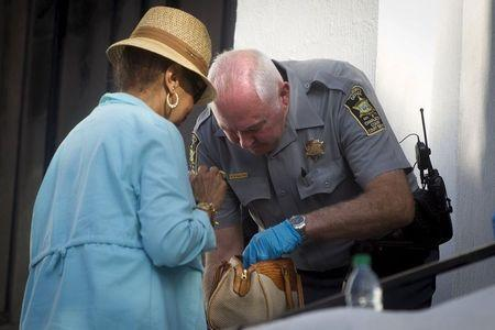 A police officer checks the purse of a parishioner as she arrives for the morning service at Emanuel African Methodist Episcopal Church in Charleston June 21, 2015.    REUTERS/Carlo Allegri