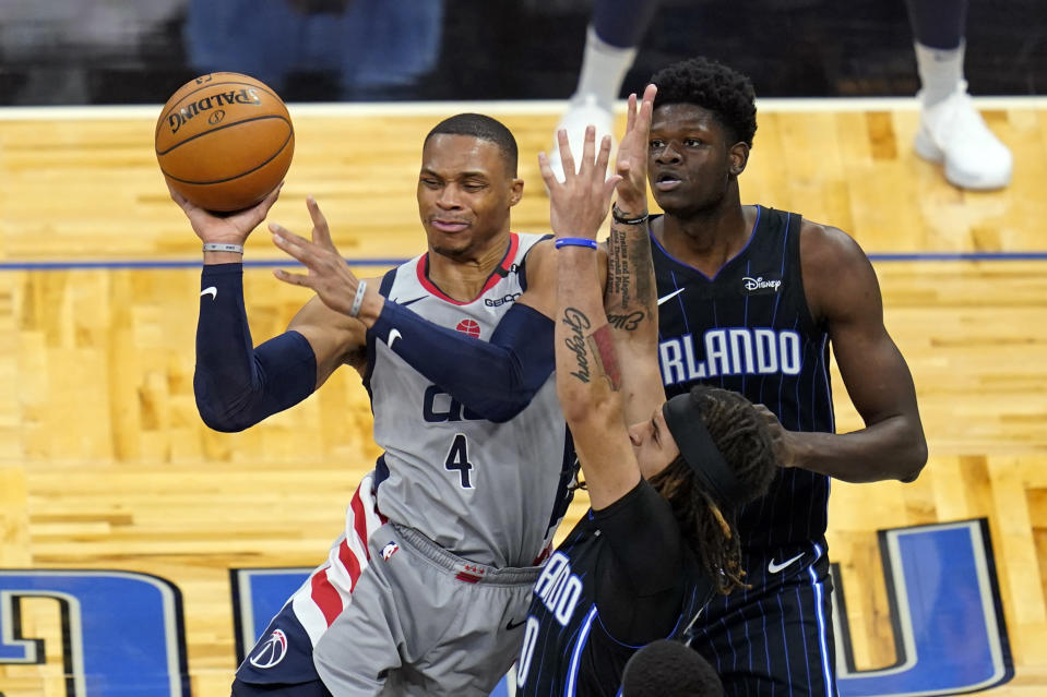 Washington Wizards guard Russell Westbrook (4) passes the ball as his path to the basket is blocked by Orlando Magic guard Cole Anthony, center, and center Mo Bamba, right, during the first half of an NBA basketball game Wednesday, April 7, 2021, in Orlando, Fla. (AP Photo/John Raoux)
