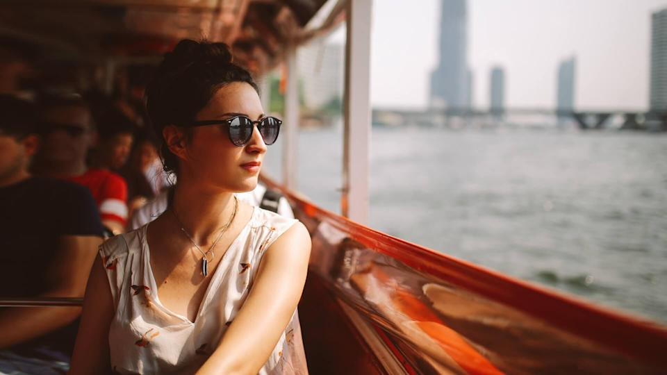Young tourist woman moving around Bangkok, using a ferry boat.