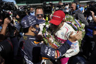 Helio Castroneves, of Brazil, is congratulated by Takuma Sato, of Japan, after Castroneves, won the Indianapolis 500 auto race at Indianapolis Motor Speedway, Sunday, May 30, 2021, in Indianapolis. (AP Photo/Darron Cummings)