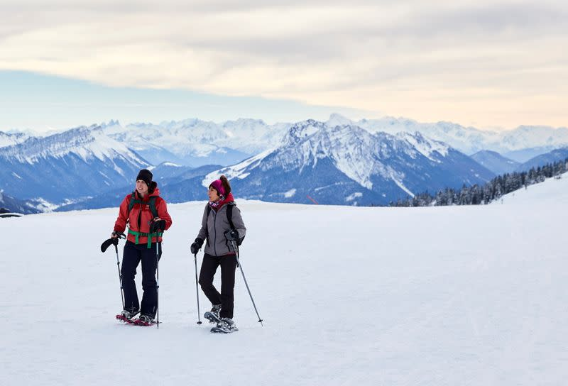 People walk with snowshoes on a winter day in Semnoz near Annecy
