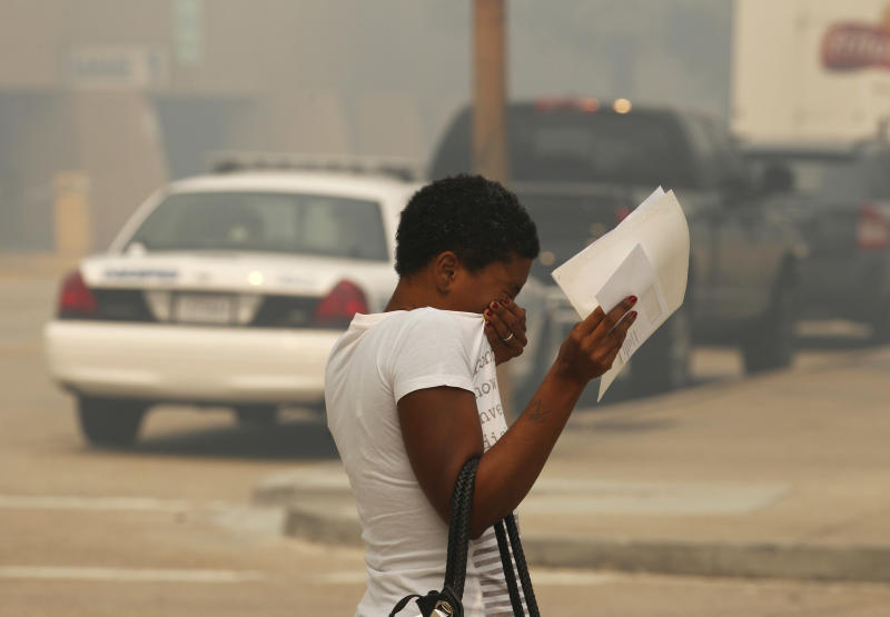 Jasmine Groves covers her face and eyes as she crosses Poydras St., amidst thick smoke from a burning marsh fire nearby, in downtown New Orleans, Tuesday, Aug. 30, 2011. Easterly winds kept a pall of smoke from the fire over the New Orleans area for the third straight day, and the National Weather Service issued a smoke alert for seven parishes.  (AP Photo/Gerald Herbert)