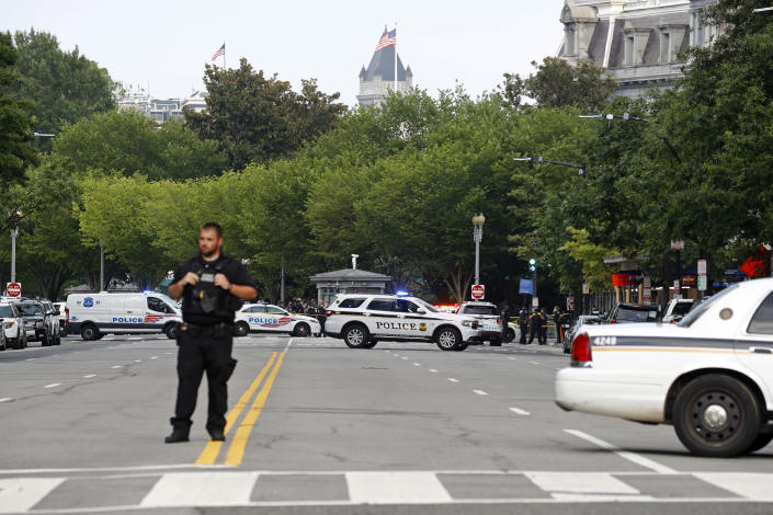 Law enforcement officials gather following a shooting that took place at 17th Street and Pennsylvania Avenue near the White House, Monday, Aug. 10, 2020, in Washington. (AP Photo/Patrick Semansky)