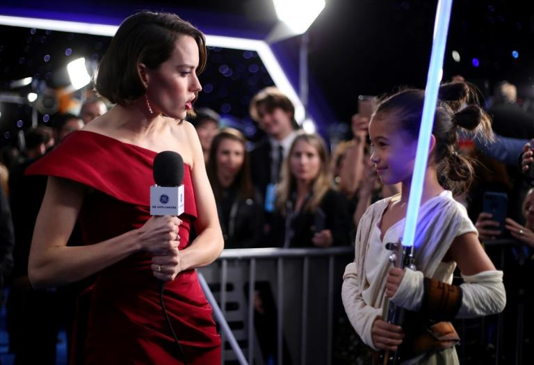 """Actor Daisy Ridley (L) meets a young admirer at the Hollywood premiere of """"Star Wars: The Rise of Skywalker"""" on December 16, 2019"""