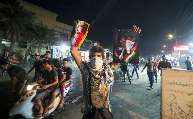 An Iraqi protester holds up a portrait of Iran's former and current supreme leaders along with an Iranian flag in Basra on September 7, 2018