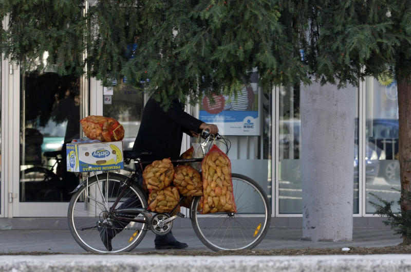 In this Oct. 22, 2012 photo a man pushing a bicycle laden with peppers in the town of Bujanovac, 340 kms south of Belgrade, Serbia. While about 99 percent of the asylum requests coming from the citizens of the Balkan nations have been rejected as unfounded, the influx has burdened the system of some EU nations, where the numbers of asylum seekers have increased ten-fold since the travel visas were abolished for much of the region in 2009. (AP Photo/Darko Vojinovic)