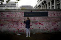 A woman speaks on a video call next to the National COVID Memorial Wall in London, Thursday, Oct. 14, 2021. (AP Photo/Matt Dunham)