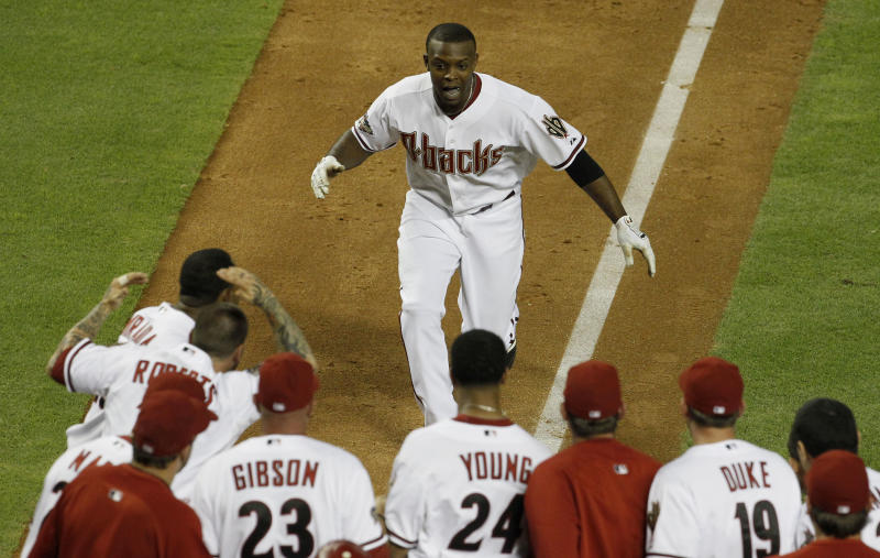 Arizona Diamondbacks' Justin Upton, top, celebrates with teammates after hitting a game-winning home run against the San Francisco Giants during the 10th inning of an MLB baseball game Thursday, June 16, 2011, in Phoenix.  The Diamondbacks defeated the Giants 3-2. (AP Photo/Ross D. Franklin)