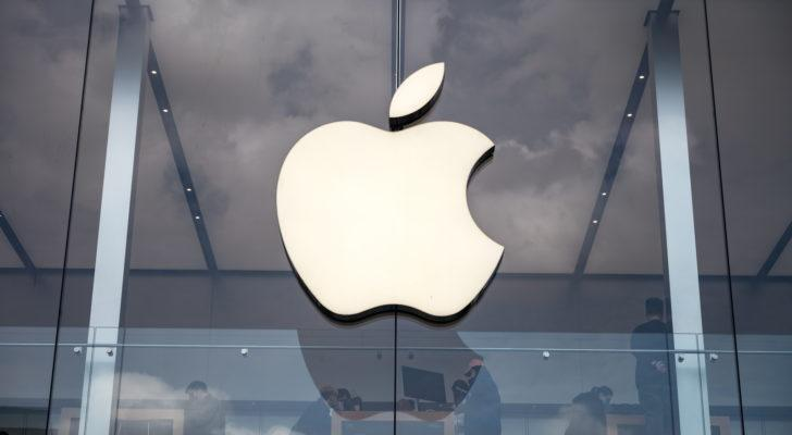 White Apple (AAPL) logo on glass with people in background