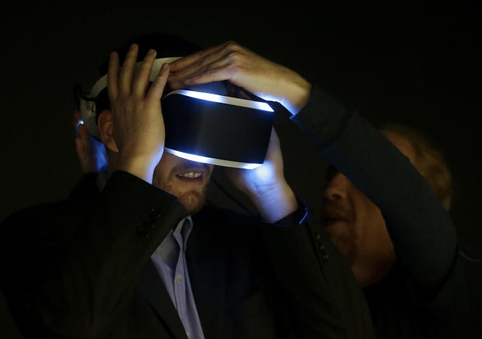 Kevin Joyce, left, gets help putting on the PlayStation 4 virtual reality headset Project Morpheus in a demo area at the Game Developers Conference 2014 in San Francisco, Wednesday, March 19, 2014. (AP Photo/Jeff Chiu)