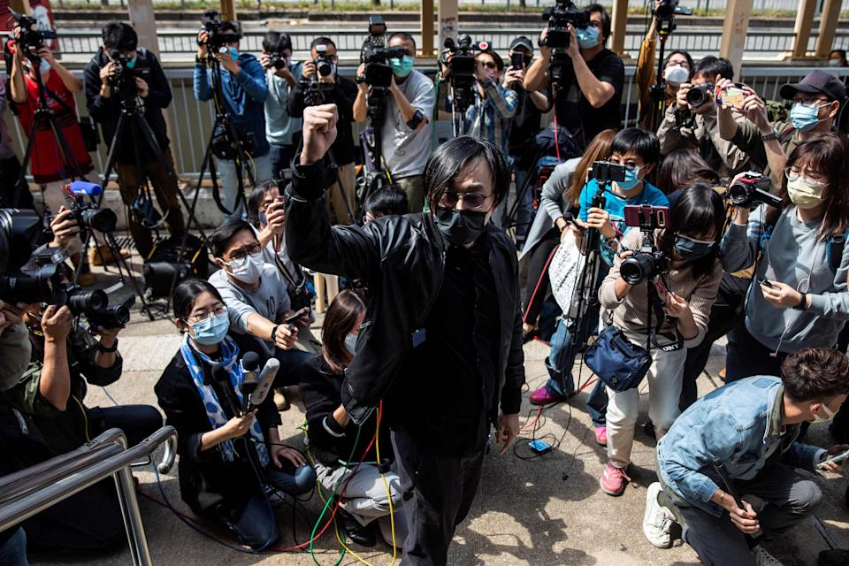 <p>Hong Kong pro-democracy activist Mike Lam gestures after speaking with the press outside Ma On Shan police station in Hong Kong where he and 46 other dissidents were each charged with one count of