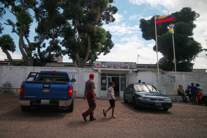 People walk past the State Police Center of Anzoategui where Giovanni Urbaneja is detained in San Jose de Guanipa