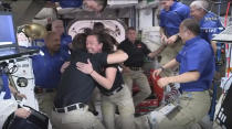 This image provided by NASA, astronauts from SpaceX are greeted by the astronauts from the International Space Station after the Dragon capsule successfully docked on Saturday, April 24, 2021. The recycled SpaceX capsule carrying four astronauts has arrived at the International Space Station, a day after launching from Florida. (NASA via AP)
