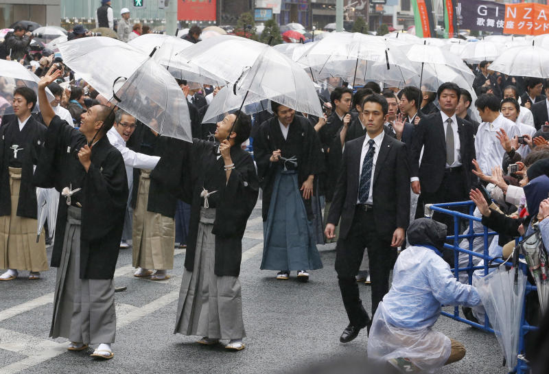 Kabuki actor Ebizo Ichikawa, left, Ennosuke Ichikawa, center, and other actors parade at Ginza shopping district in Tokyo, Wednesday, March 27, 2013. Some 60  actors paraded in the rain Wednesday to newly renovated Tokyo theatre ahead of its official opening. (AP Photo/Shizuo Kambayashi)