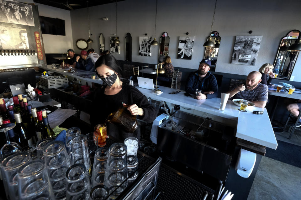 Waitress Penny Thompson prepares drinks as patrons dine at Notorious Burgers restaurant in Carlsbad, Calif., on Friday, Dec. 18, 2020. (AP Photo/Ringo H.W. Chiu)