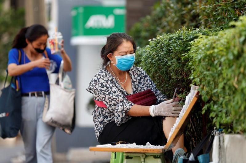 A woman sells lottery tickets on a street site as government postponed the April 1 lottery draw to May 2 due to coronavirus disease (COVID-19) outbreak, in Bangkok