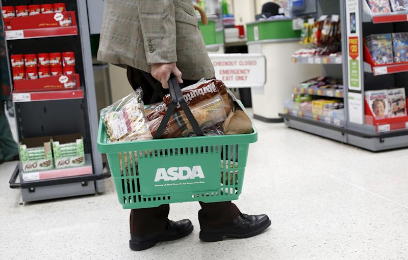 "A man carries a shopping basket in an Asda store in northwest London, Britain in this August 18, 2015 file photo. Asda is expected to report Q3 results this week. REUTERS/Suzanne Plunkett/FilesGLOBAL BUSINESS WEEK AHEAD PACKAGE - SEARCH ""BUSINESS WEEK AHEAD NOV 16"" FOR ALL IMAGES"