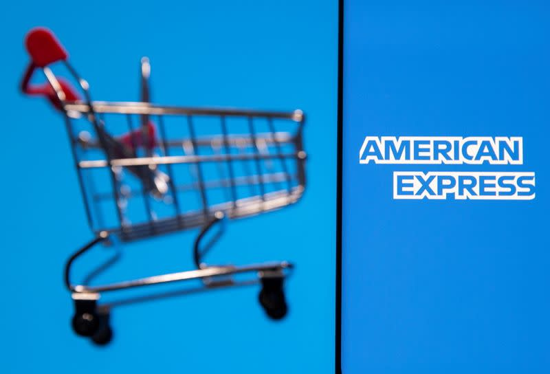 Smartphone with American Express logo is placed near toy shopping cart in this illustration