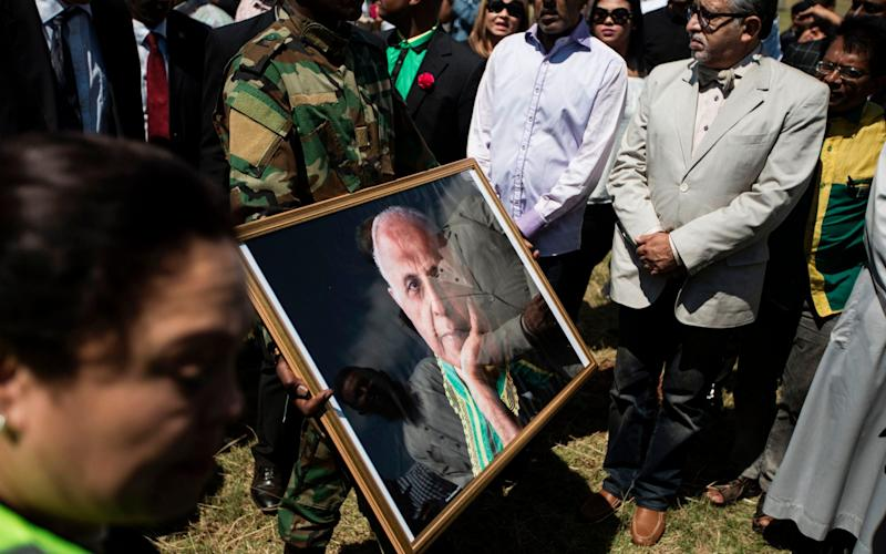 A member of former South African military wing Mkhonto We Sizwe carries the portrait of Anti-apartheid stalwart Ahmed Kathrada during the funeral - Credit: AFP