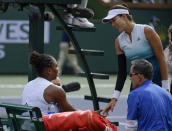Garbine Muguruza, of Spain, right, speaks with Serena Williams, left, during their match at the BNP Paribas Open tennis tournament Sunday, March 10, 2019, in Indian Wells, Calif. Williams retired from the match due to a medical issue. (AP Photo/Mark J. Terrill)
