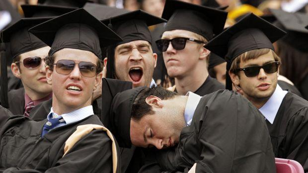 A group of college students at their graduation, with one having fallen asleep.