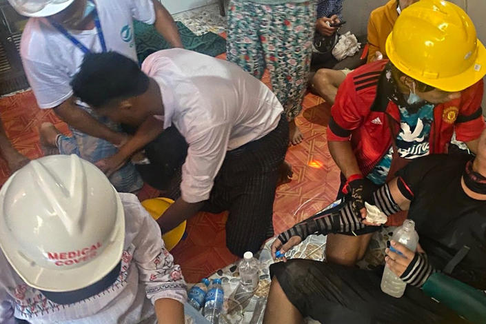 In this March 9, 2021 photo obtained by The Associated Press, doctors treat a wounded protester in a secret clinic set up in a resident's house in Yangon, Myanmar. In Myanmar, the military has declared war on health care _ and on doctors themselves, who were early and fierce opponents of the takeover in February. (AP Photo)