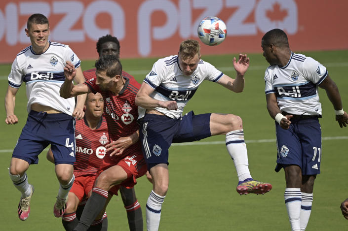 Vancouver Whitecaps midfielder Andy Rose, second from right, scores a goal in front of Toronto FC defender Omar Gonzalez (44) during the second half of an MLS soccer match, Saturday, April 24, 2021, in Orlando, Fla. (AP Photo/Phelan M. Ebenhack)