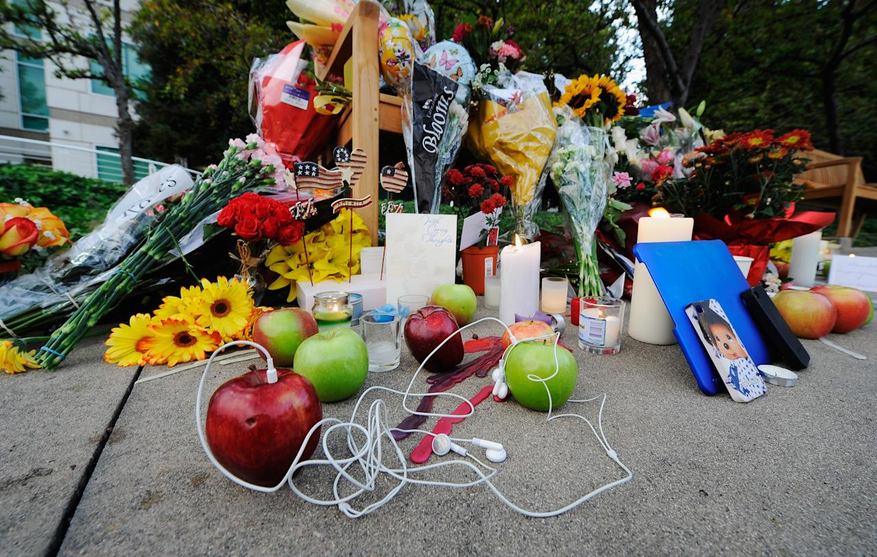 CUPERTINO, CA - OCTOBER 06:  Apples and headphones sit among cnadles and flowers at a makeshift memorial for Steve Jobs at the Apple headquarters on October 5, 2011 in Cupertino, California. Jobs, 56, died October 5, 2011.Jobs co-founded Apple in 1976 and is credited with marketing the world's first personal computer in addition to the popular iPod, iPhone and iPad.  (Photo by Kevork Djansezian/Getty Images)